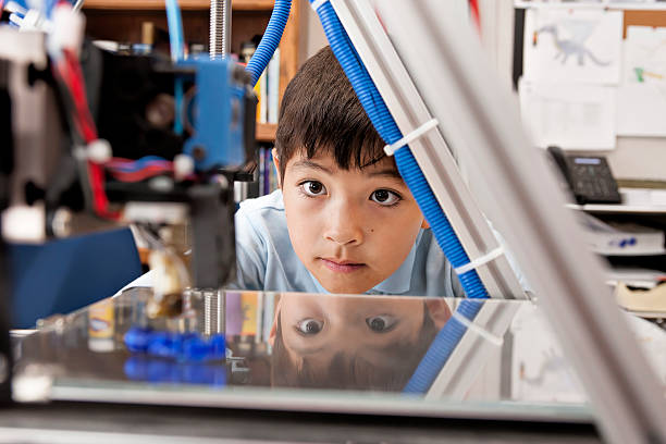 Boy watches machine intently. stock photo