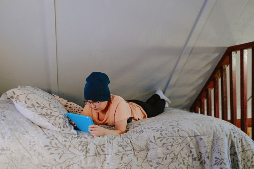 Boy watches a show on tablet while in bed