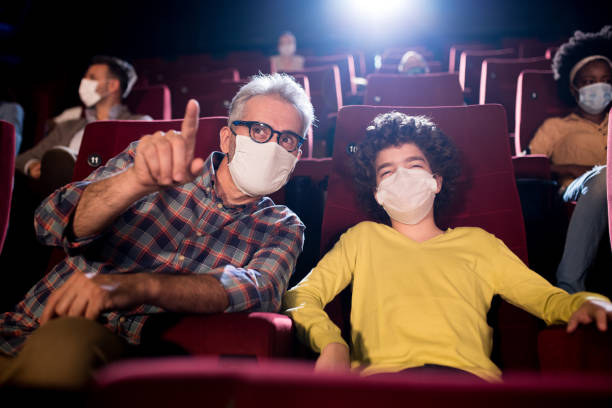 Boy watching a movie with grandpa and wearing face mask at the cinema stock photo
