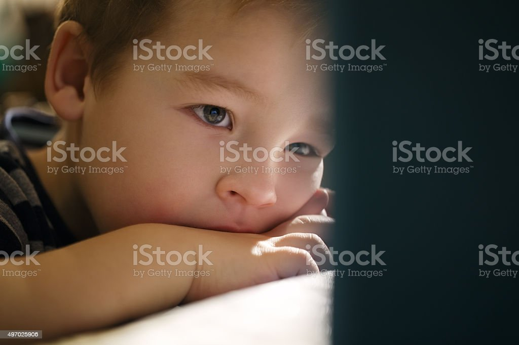Boy watching cartoons on touchpad stock photo