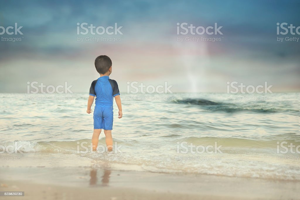 Boy watching distance whale spouting water stock photo