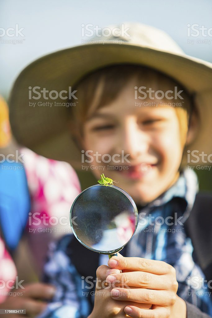 Boy watching Grasshopper standing on the magnifying glass royalty-free stock photo