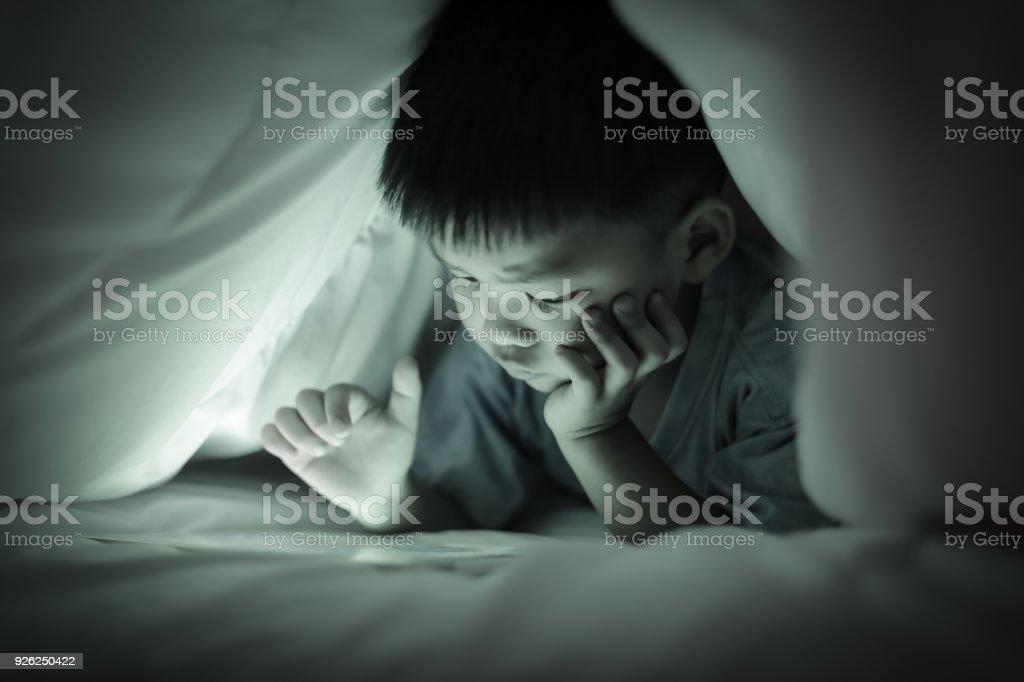 Boy watching online screen tablet, under duvet. stock photo