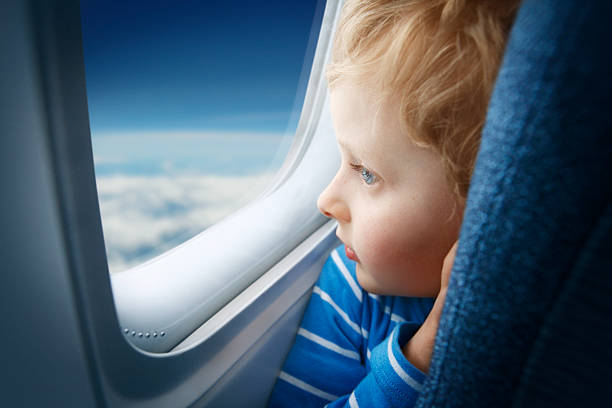 boy watching sky through the airplane window - boy looking out window stock pictures, royalty-free photos & images