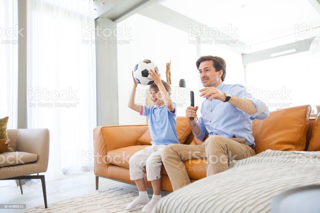 Junge beobachten Fußballspiel mit Vater – Foto