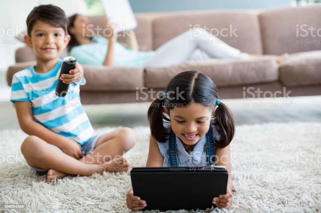 Boy watching television and girl using digital tablet in living room - Royalty-free 20-24 Years Stock Photo