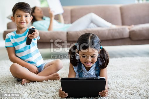 1134439364 istock photo Boy watching television and girl using digital tablet in living room 656094396