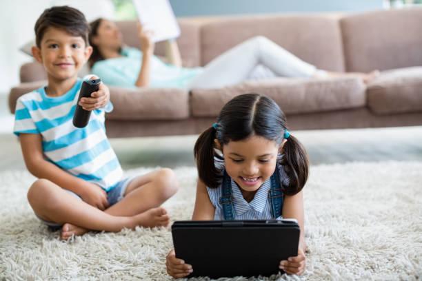 junge fernsehen und mädchen mit digital-tablette im wohnzimmer - möbel 24 online stock-fotos und bilder