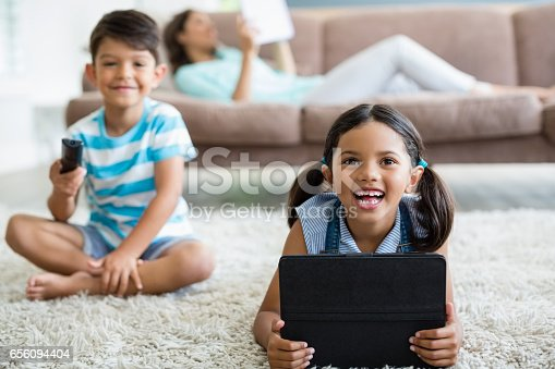 1134439364 istock photo Boy watching television and girl using digital tablet in living room 656094404