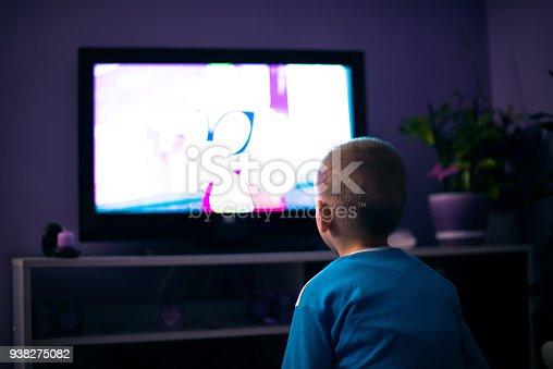 istock Boy watching television in dark 938275082