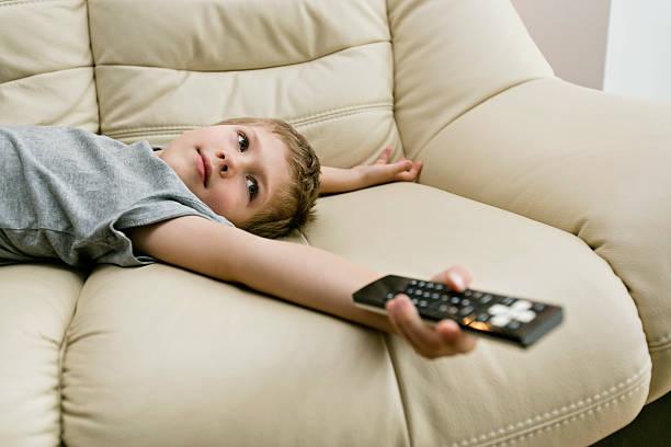 ragazzo guardando la tv - divano procrastinazione foto e immagini stock