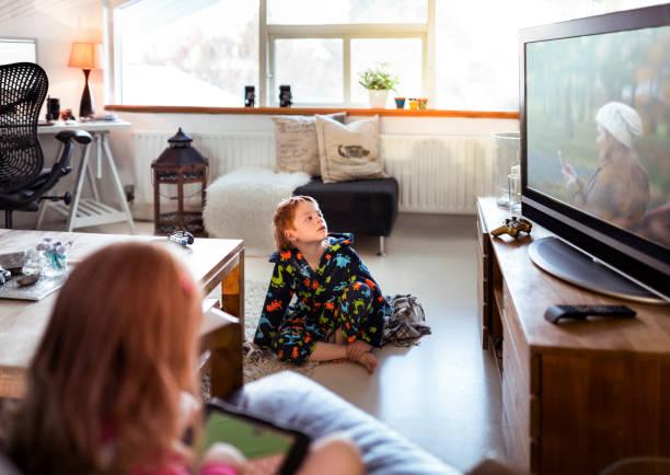 junge fernsehen beim entspannen zu hause - kids tv zimmer stock-fotos und bilder