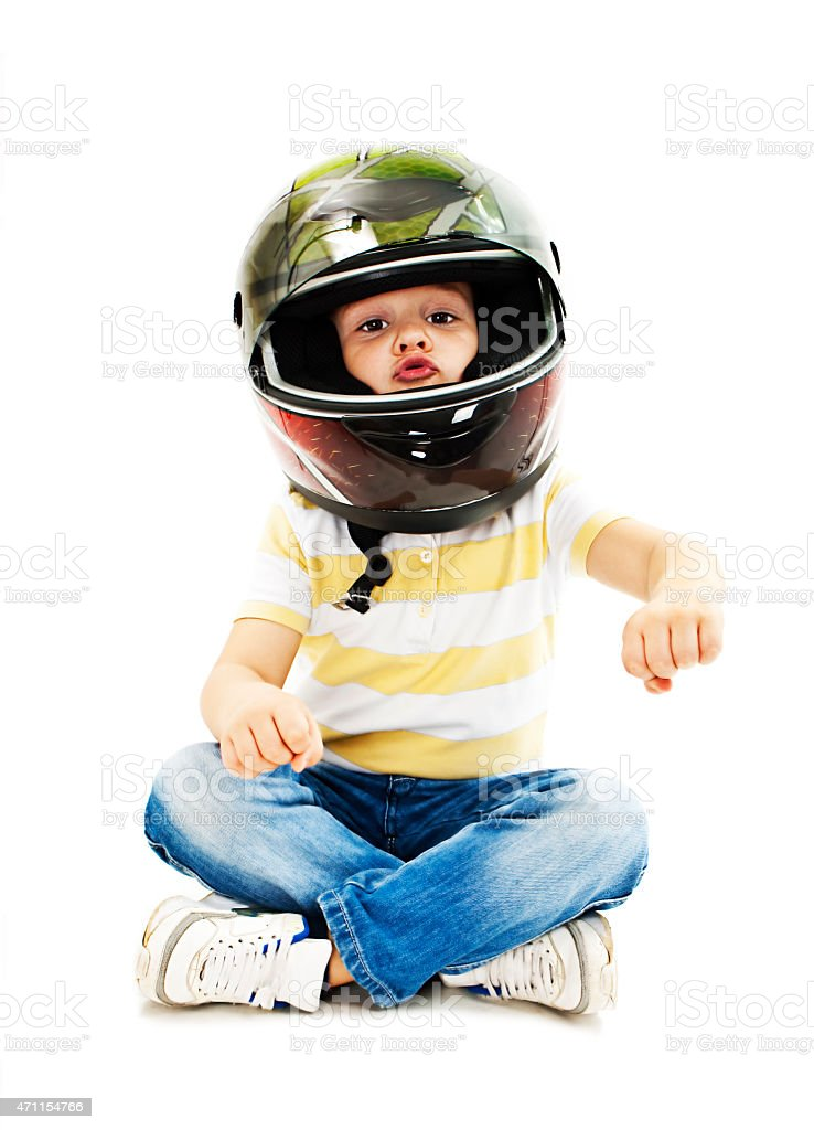 A boy wearing a helmet pretending to drive a motorcycle stock photo
