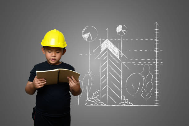 A boy wearing a yellow engineer hat and a house plan on a blackboard stock photo