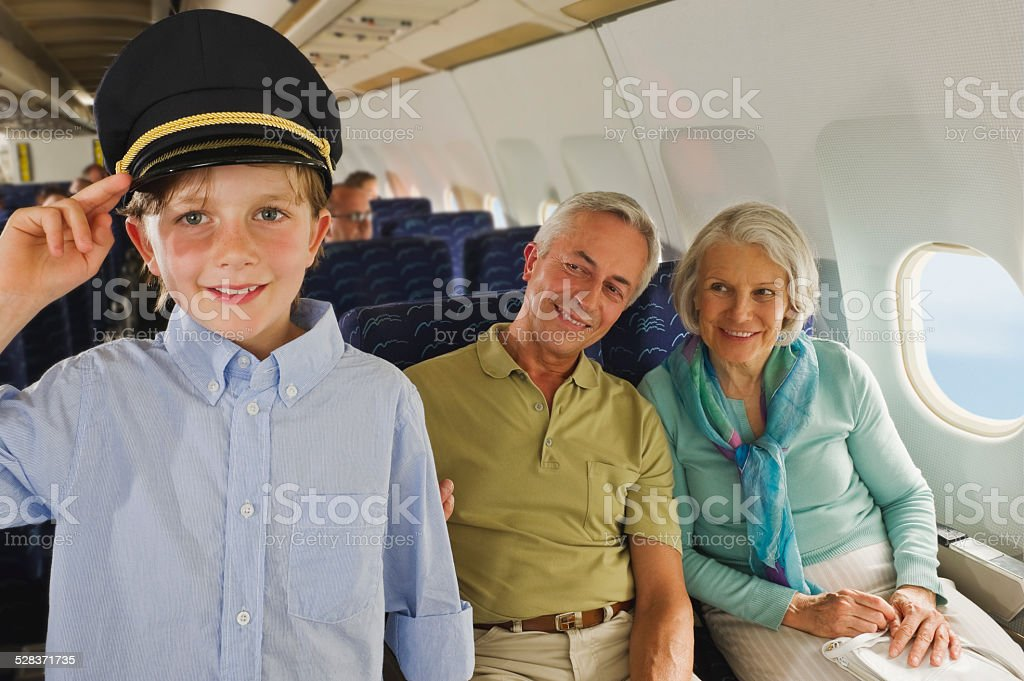 Boy wearing captains hat and people on airplane Boy wearing captains hat and people on airplane Active Seniors Stock Photo