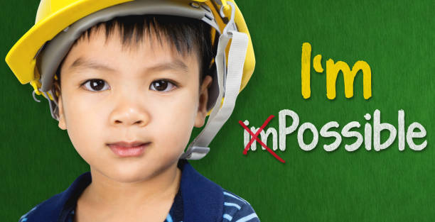 boy wearing engineering hat with im possible text for educational and occupation possibility concept - possible stock photos and pictures