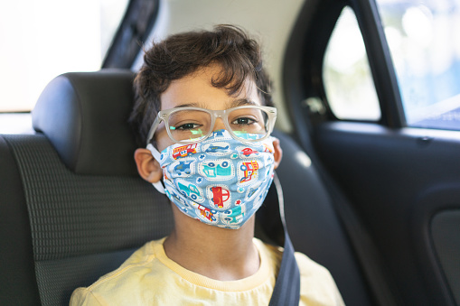Boy wearing face mask in the back seat of the car