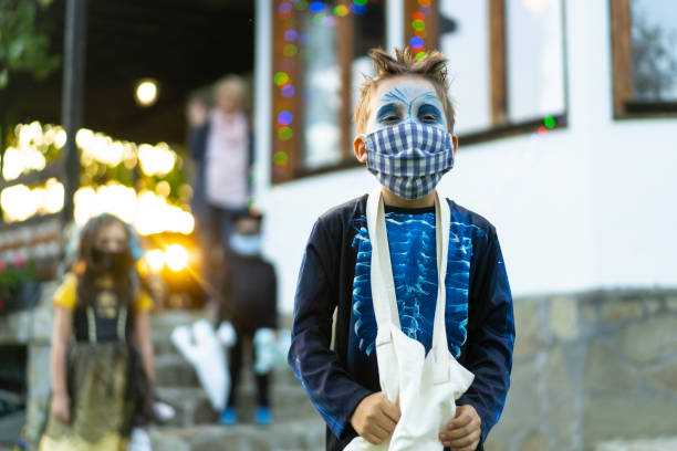Boy wearing face mask Portrait of a boy wearing face mask, trick or threating halloween covid stock pictures, royalty-free photos & images