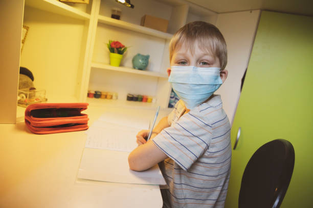 Boy wearing face masks and doing homework stock photo