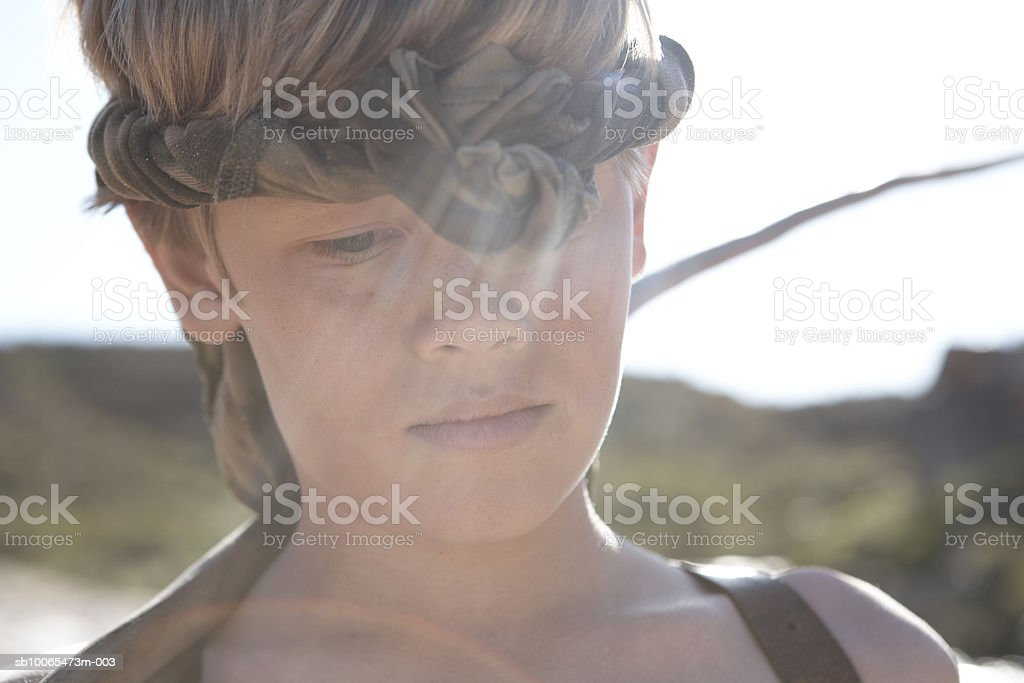 Boy (12-13) wearing headscarf looking down, close-up royalty-free stock photo