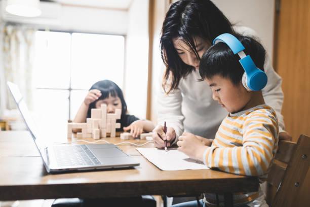 Menino usando fone de ouvido fazendo um curso de e-Learning com laptop e sua mãe assistindo - foto de acervo