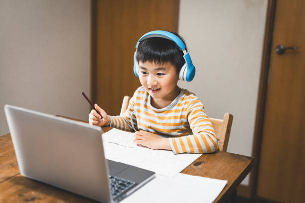Menino usando fone de ouvido fazendo um curso de e-Learning com laptop - foto de acervo
