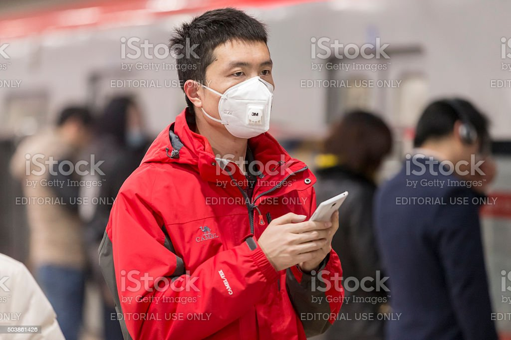 Boy wearing mouth mask with filter against air pollution, Beijing stock photo