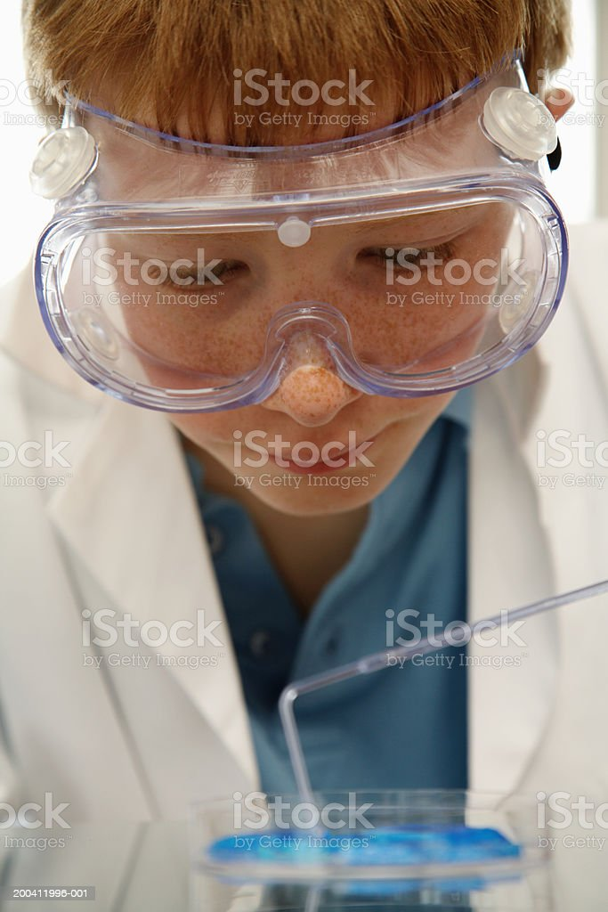 Boy (11-13) wearing protective goggles performing science experiment stock photo