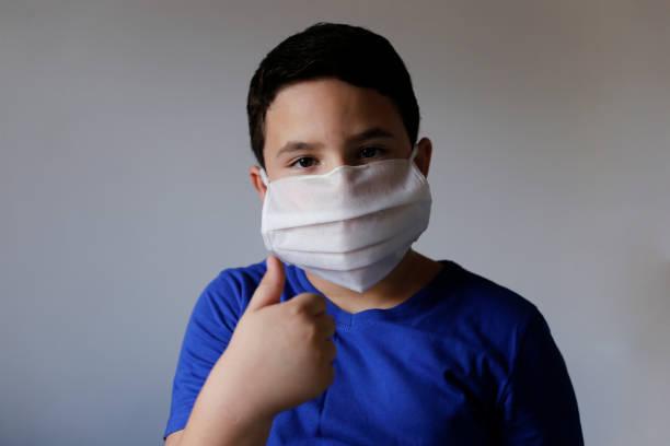 boy wearing protective medical mask stock photo