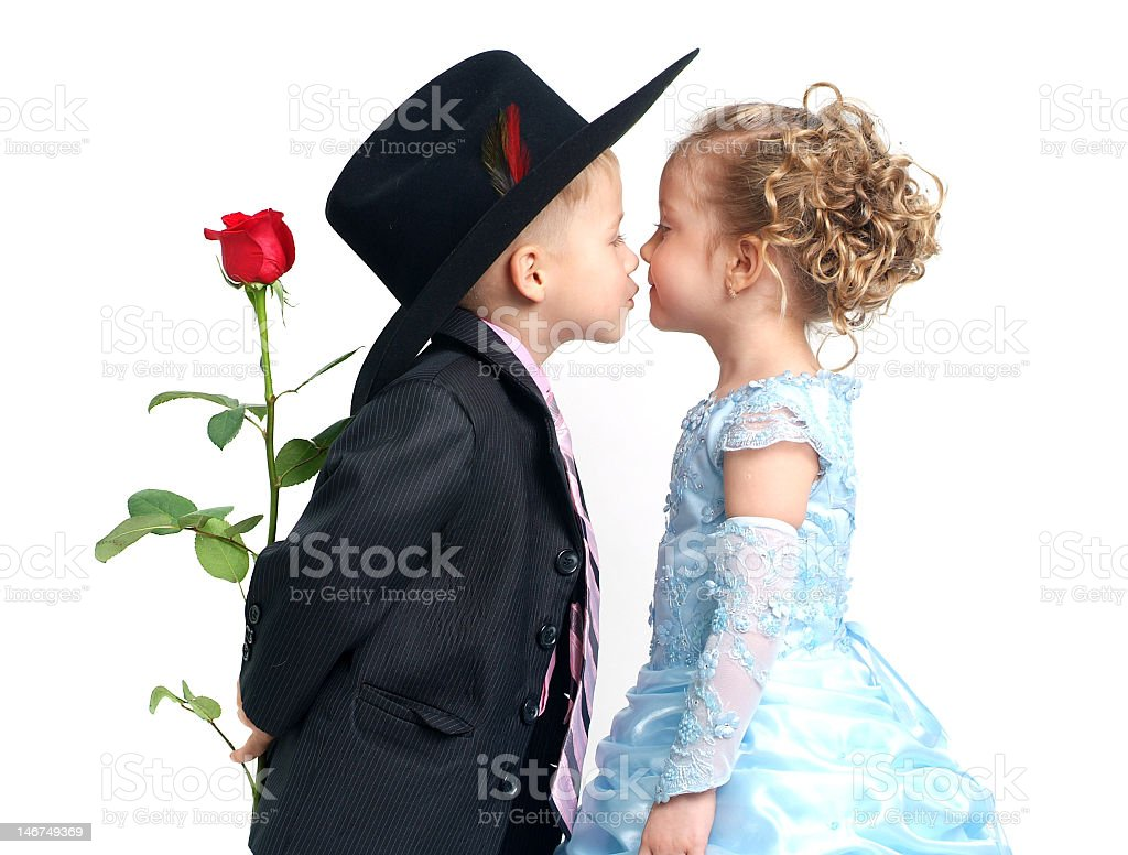 Boy wearing suit with rose behind back kissing little girl stock photo