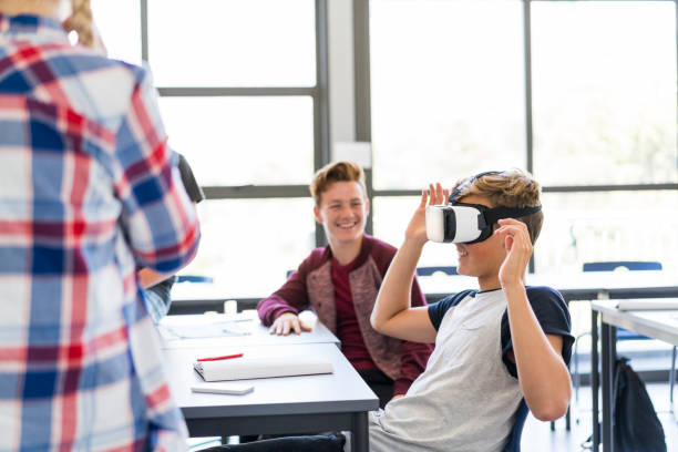 Boy wearing virtual reality headset amidst friends Friends looking at boy wearing virtual reality headset. Happy teenage students are against window in classroom. They are enjoying at high school. amidst stock pictures, royalty-free photos & images