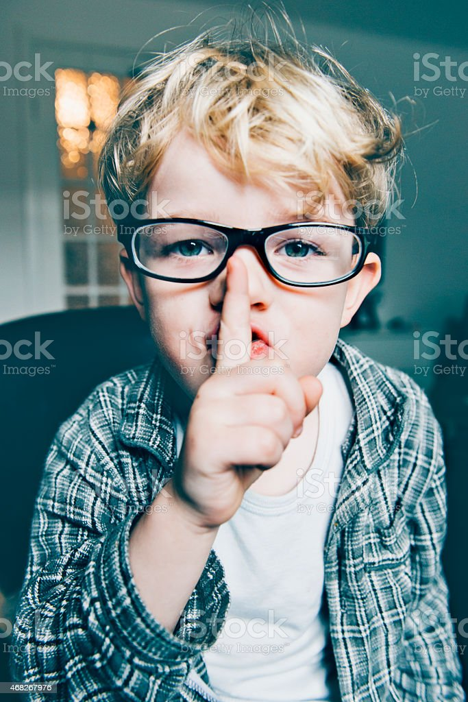 Boy wears glasses and makes a sign to be quiet stock photo