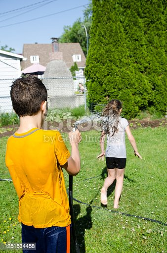 585604690 istock photo Boy wetting his sister while she's running away 1251534458