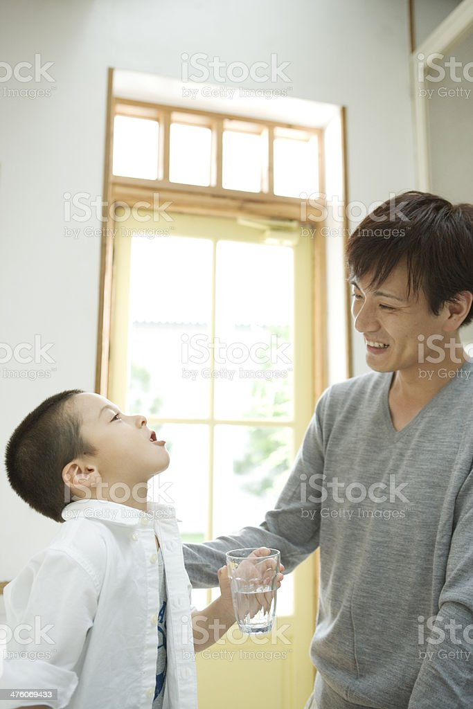 Boy who gargles with father stock photo