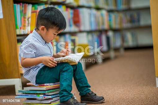 A young Asian boy is indoors in his elementary school library. He is reading a storybook while sitting on a stack of books.