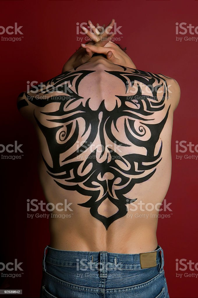 A boy whose head is bowed with a tribal tattoo on his back stock photo