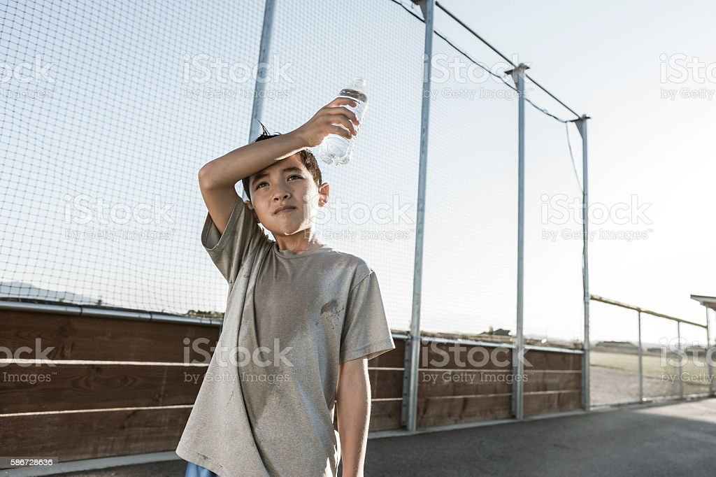 Boy wipes sweaty forehead. stock photo