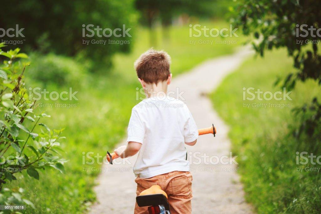 fa226fb51 Rapaz com uma bicicleta na rua. roda de bicicleta infantil foto royalty-free