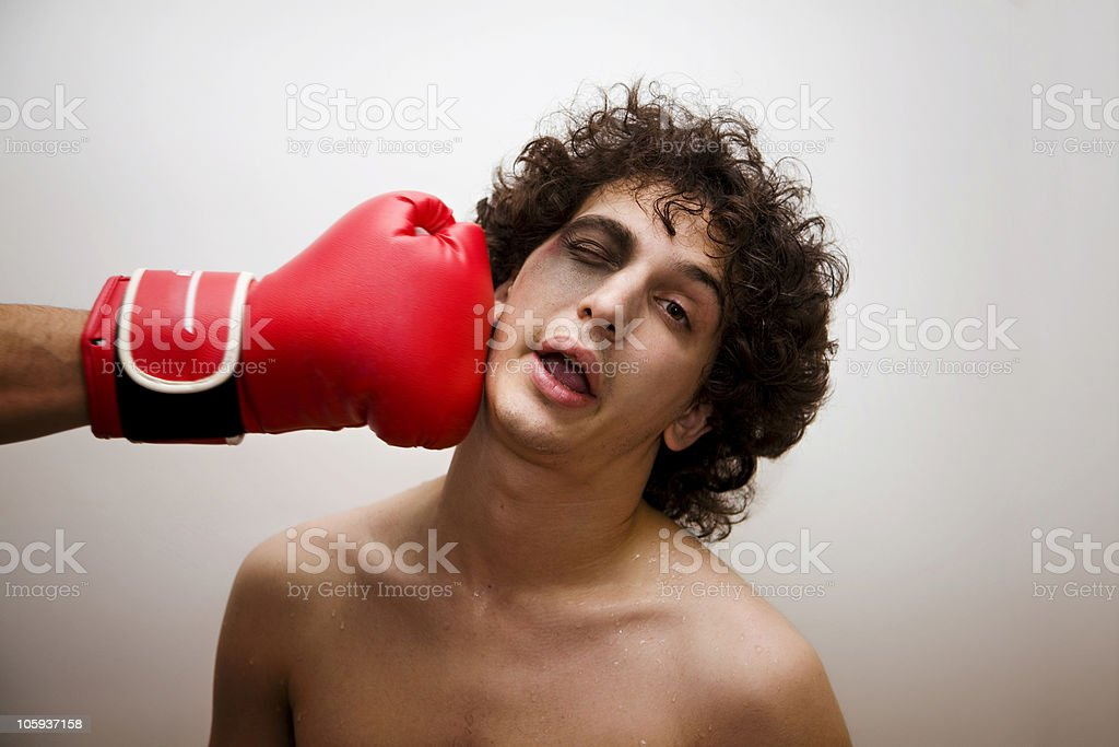 A boy with a bruised faced being punched by a boxing glove stock photo