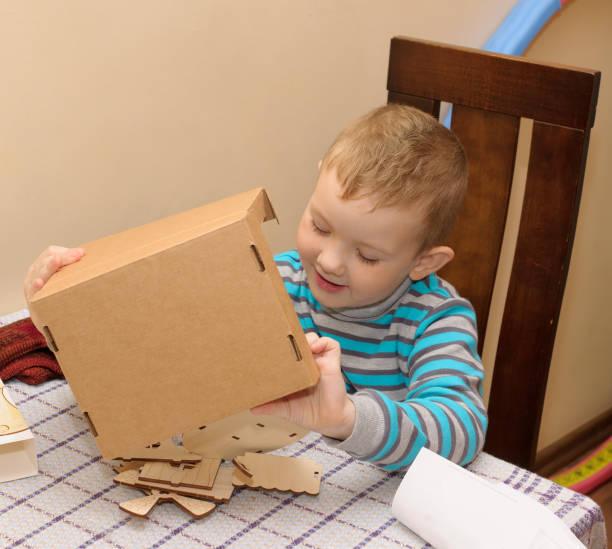 junge mit einen pappkarton - kindergarten handwerk stock-fotos und bilder