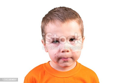 istock Boy with a closed mouth. Isolated on a white background. 1200389691