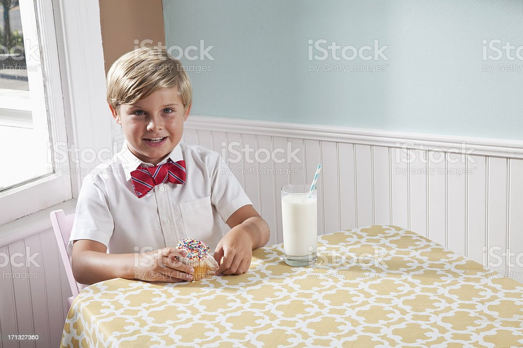 Boy with a cupcake and glass of milk stock photo