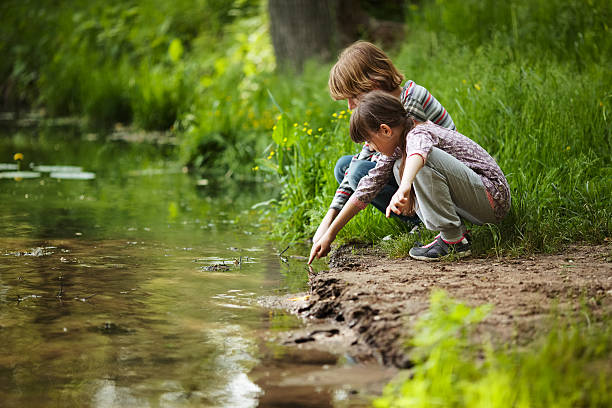 boy with a girl near the water - pond stock pictures, royalty-free photos & images
