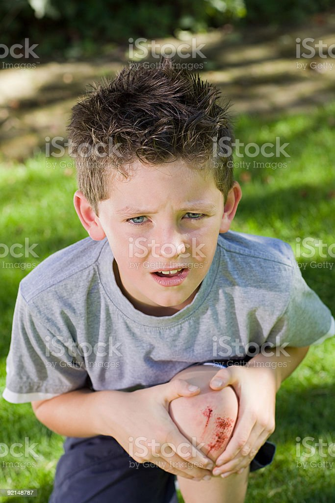 Boy with a grazed knee stock photo