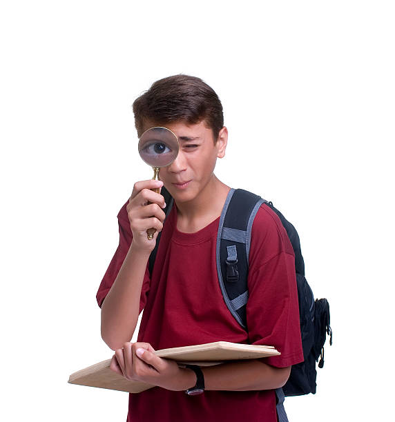 Boy with a notebook and backpack using magnifying glass stock photo