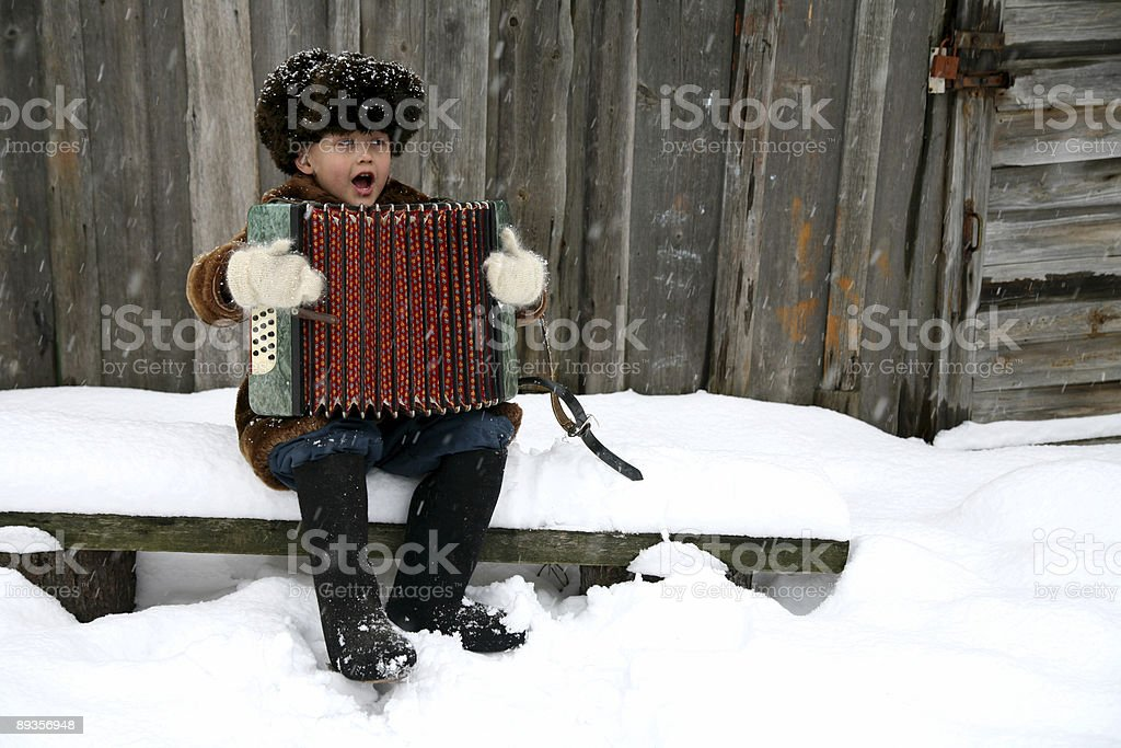 boy with accordion under snowfall royalty free stockfoto