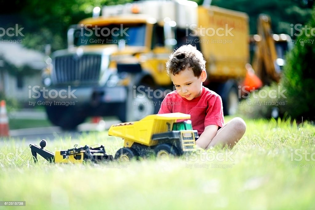 Boy with ADHD focuses his concentration on toy construction trucks stock photo