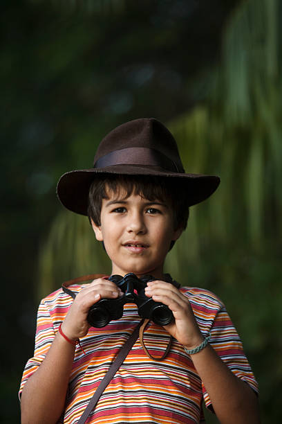 Boy with adventurer hat watching with binoculars . Boy with adventurer hat watching with binoculars . sergionicr stock pictures, royalty-free photos & images