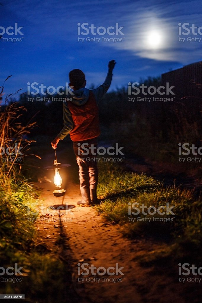 boy with an ancient candle lamp in hands outdoors stock photo