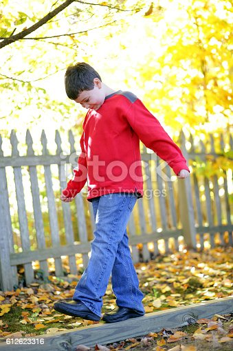istock Boy with autism carefully steps forward on outdoors balance beam 612623316
